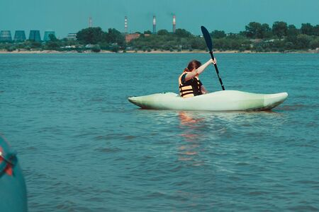Rest in the city, an active lifestyle. A girl in a kayak swims along the shore of an industrial city. Around the water, the river. In the distance smoke pipes. Sunny day.