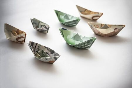 Figurines of ships made of dollars and euros. Downtime of cruise ships, cancellation of flights, financial losses, demand mode. Vignetting.