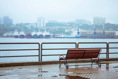 View of the seaport from the shore. In the distance are the ships, the city, modern buildings. In the foreground is a wooden bench. Overcast, it's raining, puddles. Banque d'images
