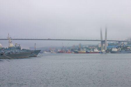Harbor view. Ships along the shore. Large modern bridge. Foggy morning.