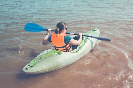 A girl in a life jacket on a kayak, in the hands of a paddle. Summer vacation, active lifestyle, weekend outdoors. View from above.