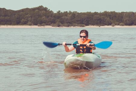 Girl on a kayak, in the hands of a paddle. Active lifestyle, sports, summer outdoor activities. Away shore, trees, sand. Solar lighting.