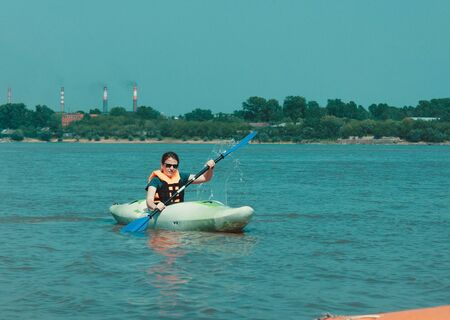 Water recreation, summer day. Girl with a paddle on a kayak. Lake, river, sea, blue water. Bright sunshine.
