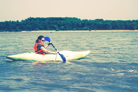 A girl in a kayak is floating on the river. Around the water. Away shore, trees, sand. Summer, activity, sport. Toning.