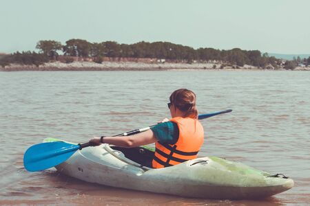 Girl with a paddle on a kayak. Orange life vest. Lifestyle, activity, outdoor recreation. Toning. Banque d'images