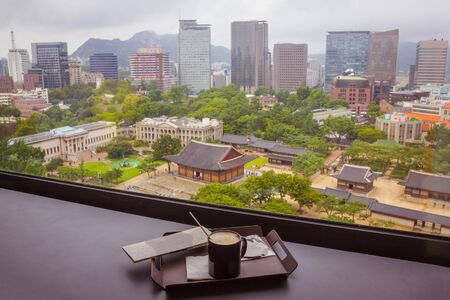 Seoul, the capital of South Korea, is the historical center. Ancient buildings mixed with skyscrapers, green trees. Away the mountains. In the foreground is a cup of coffee.