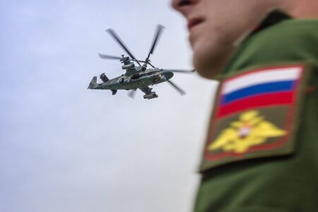 Military helicopter in the sky, aviation. In the foreground is the figure of an officer in Russian military uniform. Teachings, maneuvers. The foreground is blurred.