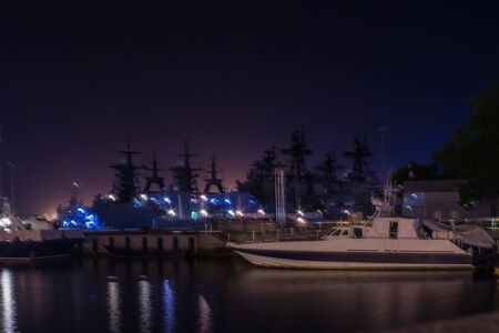 Warships in the harbor. Night, dark blue, purple sky. In the foreground is a small boat. Banque d'images