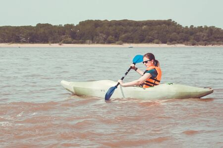 Sea, lake, wide river. A girl in a life jacket rows an oar. Away shore, trees. Hot summer day, sunny lighting. Toning.