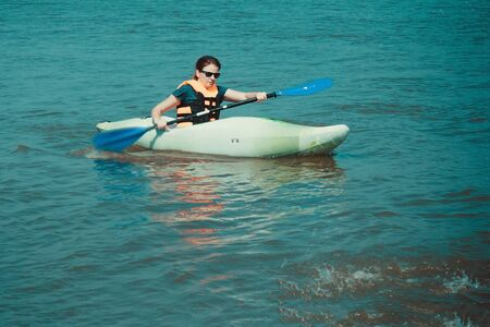 Athlete, a girl in a life jacket floats in a kayak. In the hands of the oar. Activity, water sport, relaxation. Around is blue water. Summer, heat, sunny day.