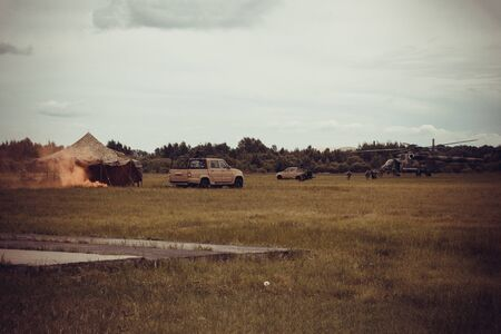 Local military operations, army exercises. On the field, a burning tent, jeeps, a helicopter in the distance, soldiers. Toning, vignetting. Banque d'images