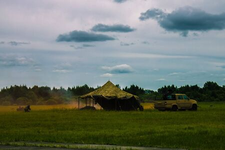 In the forest, a military tent and a car. Fleeing armed people, soldiers. Smoke from the shots. Exercises, maneuvers, army operation. Far away trees, forest. Reklamní fotografie
