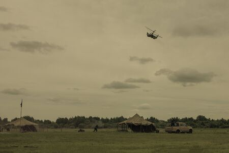 Military camp base. Armed people, car, tent. In the sky a helicopter. Local conflict, threat. Muted tones.