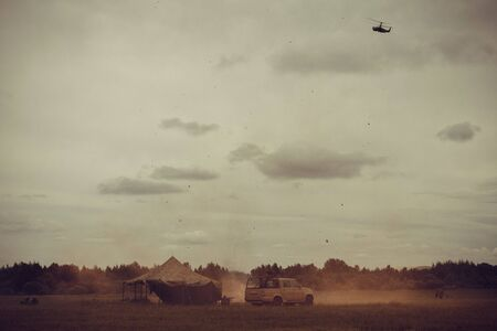 Attack on the enemy camp, military operation. In a clearing a tent and a jeep, in the distance a forest. Explosions, smoke, fire. In the sky a helicopter. Muted tones, vignetting.