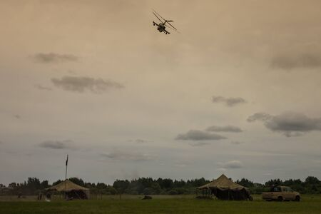 Military camp base. Tents, a car. Operation to seize the militants, local conflict. Cloudy sky, far away forest.