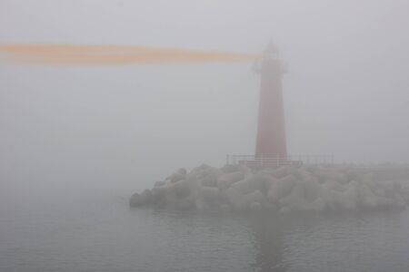 Red lighthouse in dense fog, poor visibility. Unclear outlines, contours. Muted tones, copy  space. Фото со стока