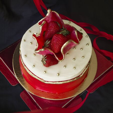 Round cake with strawberries, festive dessert. White and red. Fresh berry on top. Holiday, celebration, birthday. Black background.