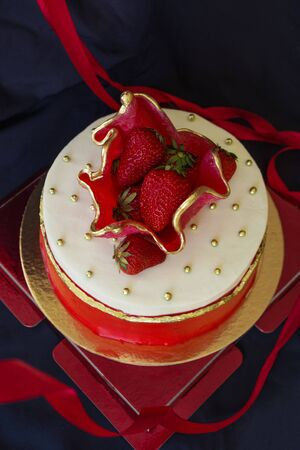 Cake with strawberries, white and red. The top is decorated with fresh berries and golden beads. Holiday, celebration. View from above.