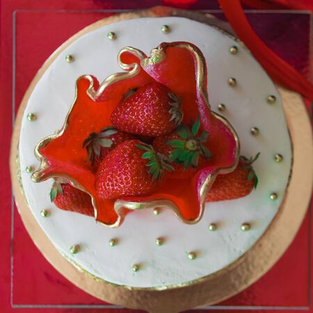 Dessert, a sweet dish. Round summer cake with fresh strawberries. Red, white and gold colors. Tasty, sweet, luxurious. View from above.