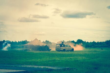 Military camp, smoke after the explosion. Teachings, military operation, capture of the enemy. Around the green grass, away the forest. Cloudy sky. Stock Photo