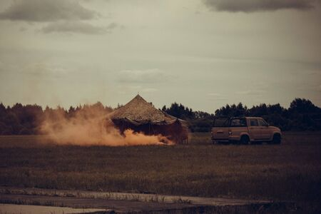 Military camp, base, next to the tent  . Orange fire, smoke. Attack, threat. Away the forest. Muted tones, vignetting. Фото со стока