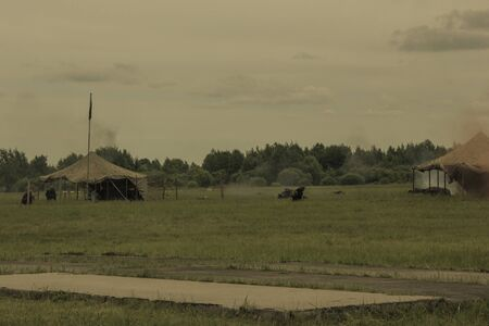 Training camp, tents. Military operation, smoke. Summer day. Muted tones. Фото со стока