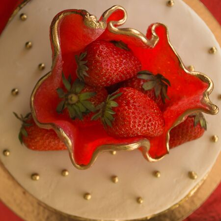 Beautiful, delicious cake with strawberries. Summer, festive mood. Red, white and gold color, decoration. View from above. Banque d'images