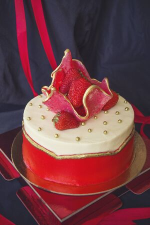 Holiday cake on a black background. The top is decorated with fresh strawberries. Holiday, celebration, sweet gift. Side lighting.