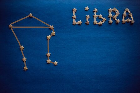 On a blue background a constellation of Libra is schematically laid out. The sign of the air element. Copy space, top view. The picture is made by the author.