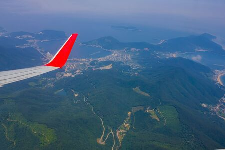 Travel, voyage, flight by plane. View from the porthole. Below are green mountains, the sea. Air transport. Фото со стока