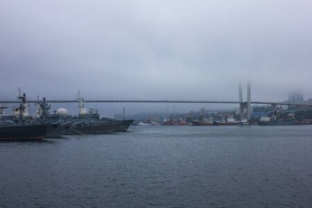 Bridge over the Golden Horn Bay, Vladivostok. Cargo and warships in the roads. The view from the water. Fog, cloudy day.