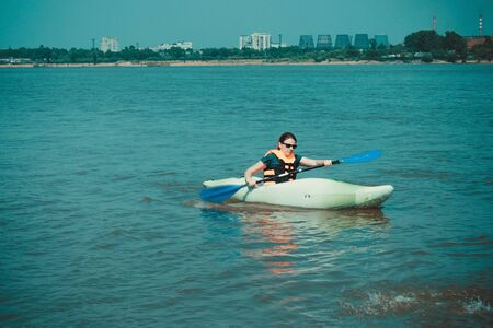 Girl on a kayak floats away from the industrial city. Away on the shore of the industrial zone, factory, pipes. Around is blue water. Summer is a sunny day. Фото со стока