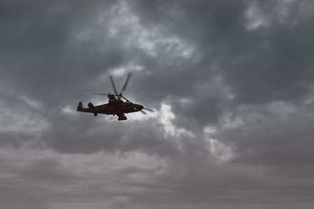 Army aviation, air transport. Helicopter flight against a cloudy sky. View from below. Toning. Copy space. Фото со стока