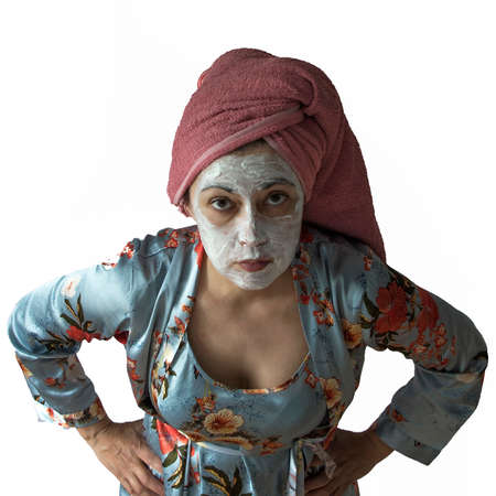 A woman in blue pajamas, a cosmetic mask on her face. Hands on hips, eyes have a question and suspicion. Family relations, disgusting wife. 写真素材
