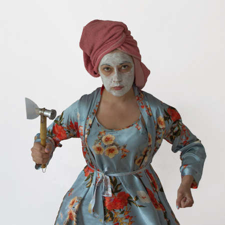 Woman in home clothes holding a kitchen ax. Aggression in the family, violence, showdown, conflict.