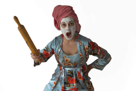 An angry wife attacks. Awesome pose, in the hands of wooden utensils. Family conflict, quarrel.