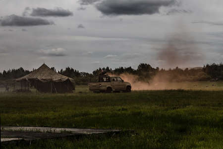 Tent, car, armed people. Green field, all in smoke. Military operation, capture of fighters, attack. Cloudy sky, muted tones. Stock Photo