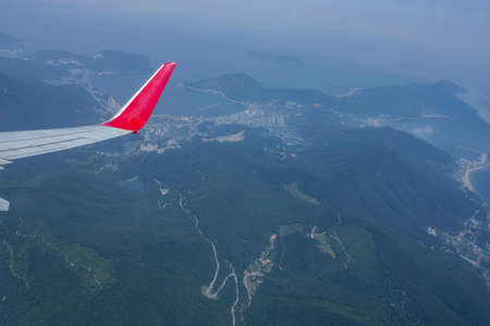 Flight by plane, travel. The airplane wing is visible from the porthole. Below are green mountains, forest, sea.