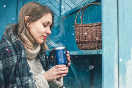 A woman in a plaid is drinking tea on the porch of a village house. Cold snap, autumn, winter.