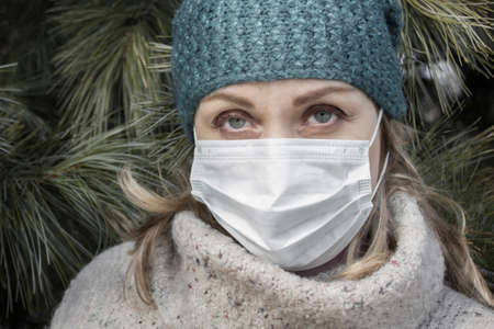 Epidemic of colds, protection from infection. A woman in a hat and a warm sweater against the background of a green coniferous tree. Anxiety in the eyes.