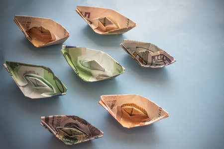 Cancellation of cruise flights, losses of shipping companies. Ships made of notes, euros and dollars. Copy space. Top view, vignetting.