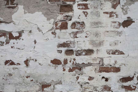 The red brick wall is covered with white plaster. Peeling uneven surface.