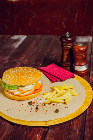 Burger with beef, fried bacon, onion, tomato, lettuce and marinated cucumber on wooden background with copy space