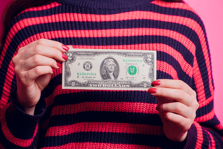 Hand holding two dollar bill. Isolated on a colored sweater. Stock Photo