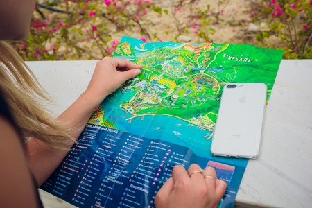 NHA TRANG,VIETNAM - FEBRUARY 17,2018: girls tourists are studying the map of the water park of attractions Editorial