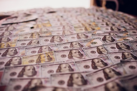 Hundreds of new Benjamin Franklin 100 dollar bills arranged randomly with the portrait facing uppermost in a conceptual financial and monetary background Reklamní fotografie