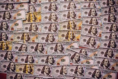 Hundreds of new Benjamin Franklin 100 dollar bills arranged randomly with the portrait facing uppermost in a conceptual financial and monetary background Stock fotó