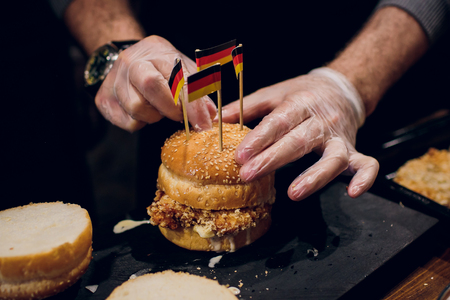 Closeup of home made beef burgers with volatile, onions, and mayonnaise served with a knife stuck on little wooden cutting board. Dark background food Stock Photo