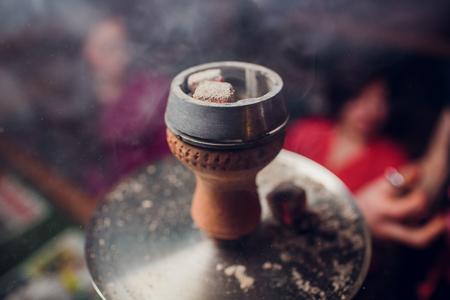 Preparing the shisha, aka nargile or hookah at a restaurant by placing the charcoals on top.