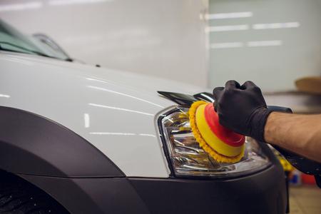 auto mechanic buffing and polishing car headlight Car detailing - man with orbital polisher in auto repair shop. Selective focus. Standard-Bild - 99986575